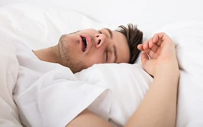 young man sleeps hard while snoring with his mouth wide open