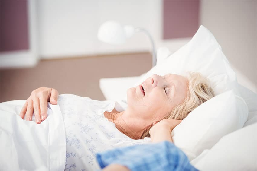 Older woman snores loudly in bed